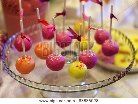 Colorful cake-pops on a glass plate