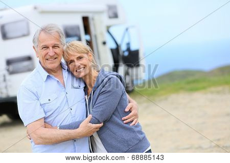 Cheerful senior couple standing by camper on road stop