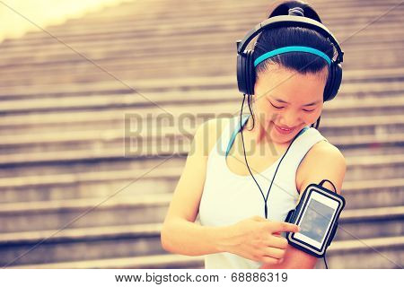 Runner athlete listening to music in headphones from smart phone mp3 player smart phone armband.
