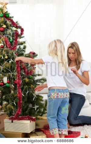 Blond Little Girl And Her Mother Decorating Christmas Tree