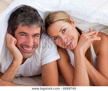 Enamoured Couple Having Fun Lying On Bed