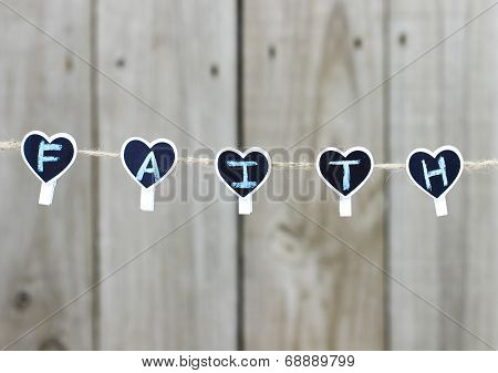 FAITH hearts hanging on clothesline with wooden background