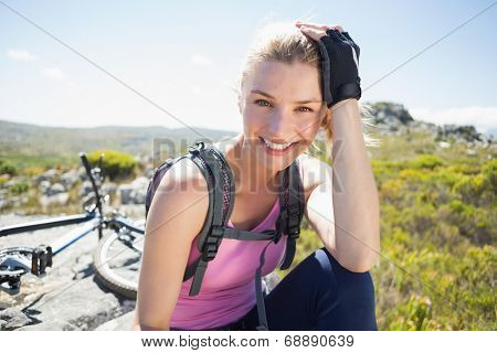 Fit pretty cyclist taking a break on rocky peak smiling at camera on a sunny day
