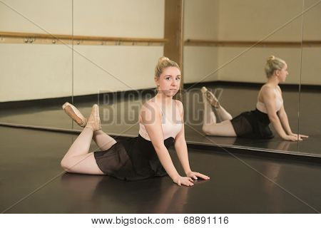 Beautiful ballerina posing in front of mirror in the dance studio