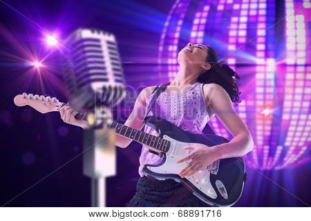 Pretty girl playing guitar against digitally generated cool disco ball design