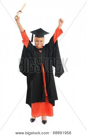 Portrait of full length smiling Asian female Muslim student in graduate gown hands raised showing graduation diploma standing isolated on white background.