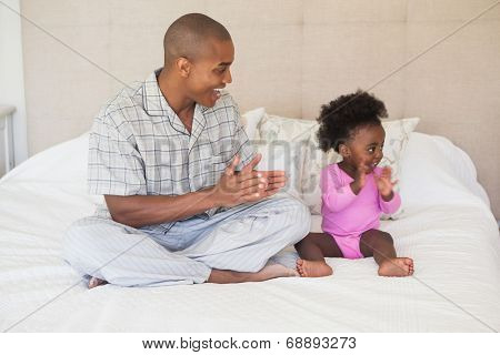 Father and baby girl sitting on bed together at home in the bedroom