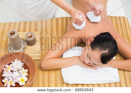Peaceful brunette enjoying a herbal compress massage in the health spa