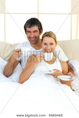 Enthusiastic Lovers Drinking Coffee Lying In The Bed