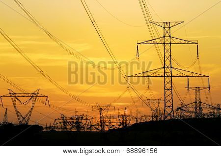 Field Of High Voltage Towers Under Dramatic Sky