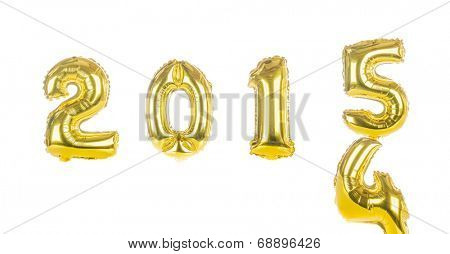 2015 in gold foil balloons bringing in the new year over 2014 isolated on white