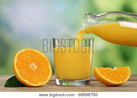 Orange Juice Pouring Into A Glass In Summer