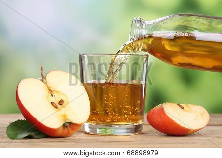 Apple Juice Pouring From Red Apples Into A Glass