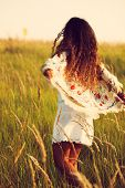 image of hair motion  - woman wearing boho style clothes run through the grass - JPG