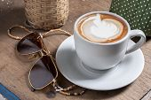 stock photo of latte  - Coffee Latte in a white cup with sunglasses - JPG