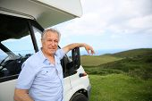 stock photo of camper  - Senior man standing by camper - JPG