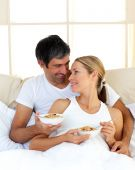 Cheerful Lovers Eating Cereals Lying In The Bed