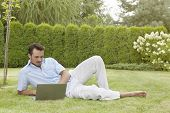 stock photo of recliner  - Full length of young man using laptop while reclining in park - JPG