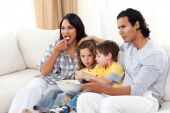 Lively Family Watching Tv On Sofa