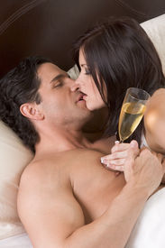 stock photo of lewd  - Young sexy heterosexual couple celebrating with wine in bed - JPG