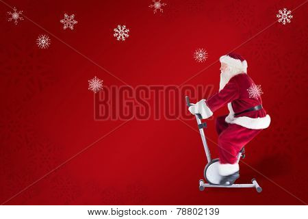 Santa uses a home trainer against red snowflake background