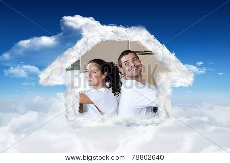 Radiant couple with unpacking boxes moving to a new house against bright blue sky with clouds