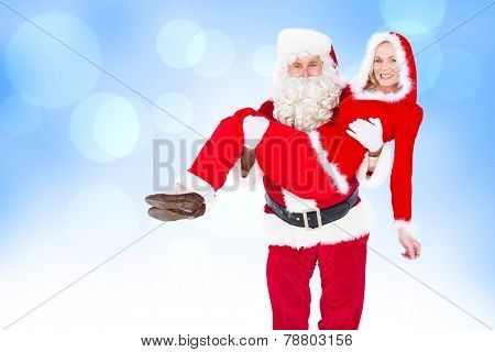 Santa and Mrs Claus smiling at camera against blue abstract light spot design