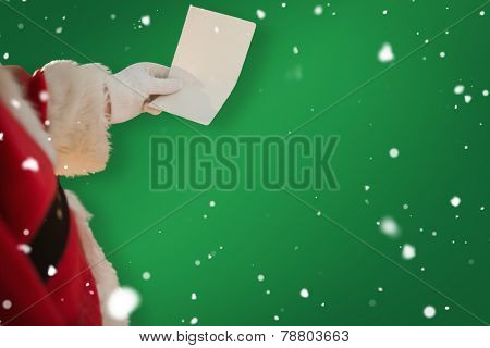 Father christmas holding a paper against green