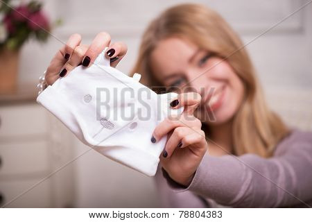 Young attractive woman holding baby hat , interior shot
