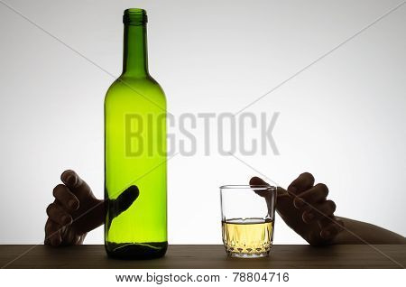Hands Reaching For A Glass And A Bottle