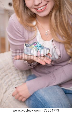 Young attractive woman holding baby shoe, interior shot
