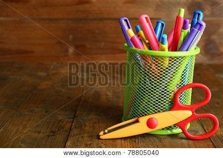 Metal holder with different pens and scissors on rustic wooden background