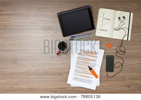 Exam week background, with various study tems, such as a highlighted reader with standard (lorum ipsum) text, a cup of coffee, electronic tablets, music player and ear plugs, and a calendar
