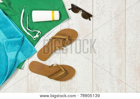 Colorful background image with basic summer vacation items, such as swimming shorts, a towel, sunglasses, sun block and flip flop slippers