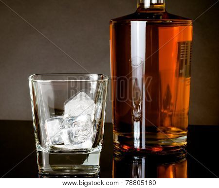 Empty Whiskey Glass With Ice Near Bottle On Black Background