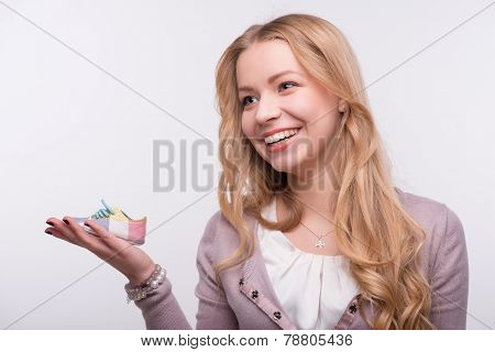 Young attractive woman holding baby shoe isolated on white backg