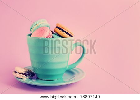Assortment of gentle colorful macaroons in mug on pink background