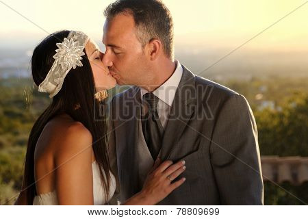 Bride And Groom Kissing At Sunset At A Viewpoint