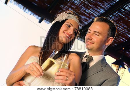 Groom And Bride Toasting On A Terrace Smiling Eye Contact