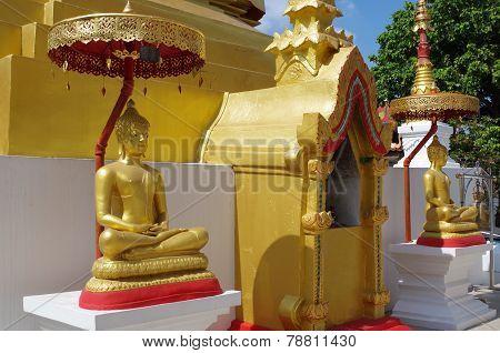 2 Gold Buddha underneath umbrellas.