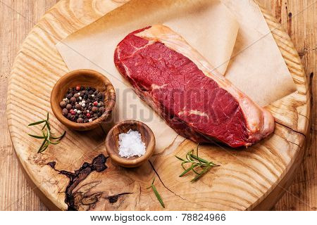 Raw Fresh Meat Striploin Steak With Salt And Pepper On Wooden Background
