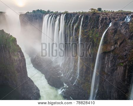 Victoria Falls sunset, Zambia side with zambezi river, red sun, long exposure
