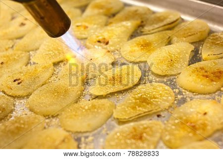 Detail of blowtorch caramelising sugar on pear slices.