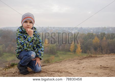 Cute boy child outdoors. Misty wood on the background.