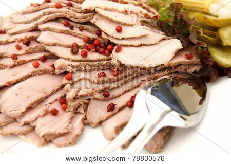 Plate of cold meat slices with cutlery.