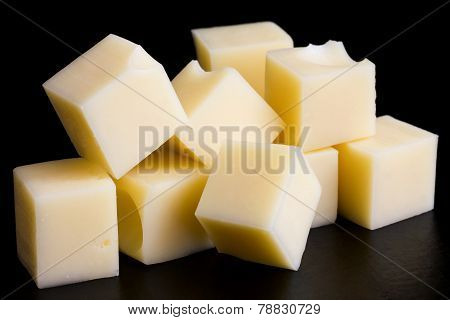 Small yellow cheese cubes on black surface.