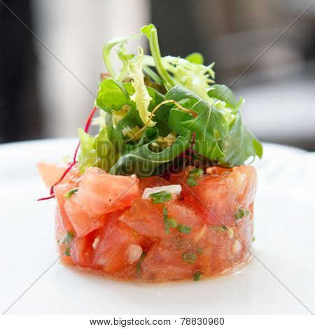 Tomato tartare topped with green salad