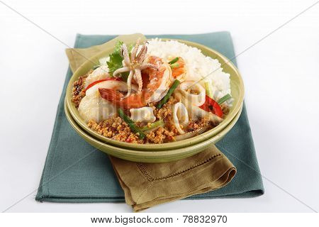 Fried seafood with curry powder on dish with rice