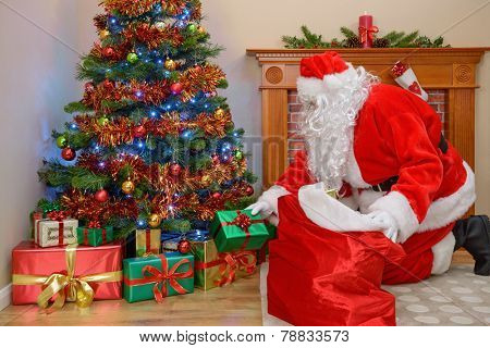 Santa Claus or Father Christmas putting gifts under the tree