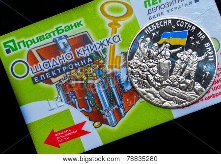 Kiev,Ukraine.Dec 22.Illustrative editorial.Ukrainian commemorative coin in memory Revolution of Dignity with card of Privat Bank as background .At December 22,2014 in Kiev, Ukraine